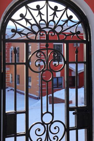 rejas de hierro: Niza portillo forjado de la vendimia contra patio con edificio rojo
