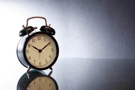 minute hand: Black alarm clock with reverberation on dark background Stock Photo