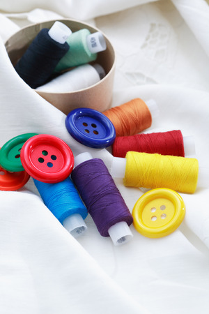 needlecraft product: Set of colored thread and buttons on white textile Stock Photo