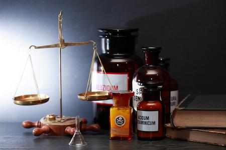 balanza de laboratorio: frascos farmacéuticos viejas acercan a escala de peso y libros