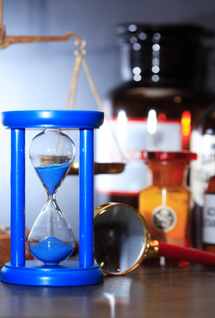 Blue hourglass against flasks near weight scale and magnifying glass