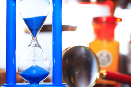 Blue hourglass against blurred background with flasks and magnifying glass