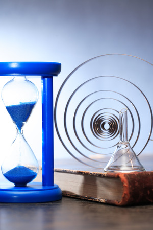 Education concept. Blue hourglass on old book near metal spiral Imagens