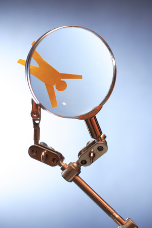 totalitarianism: Human rights concept. Yellow paper man in metal clamping device under magnifying glass Stock Photo