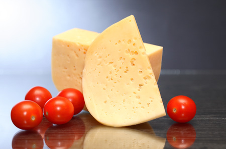 reverberation: Piece of cheese and tomatoes on nice dark background with reverberation