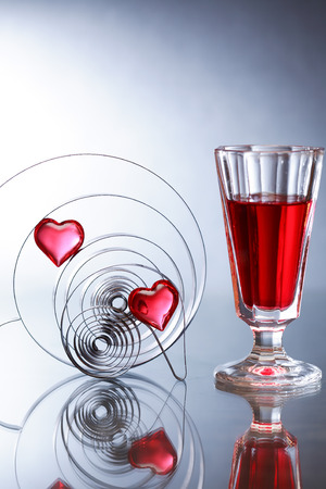 Two red glass hearts inside metal springs near wineglass on nice gray background