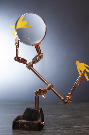 totalitarianism: Yellow paper man in metal clamping device under magnifying glass