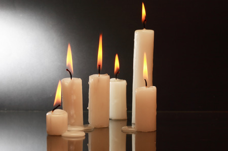 lighting background: Few lighting candles with reflection on dark background Stock Photo