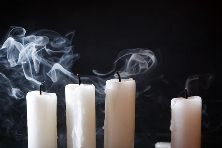 blackout: Few extinguished candles in a row on dark background