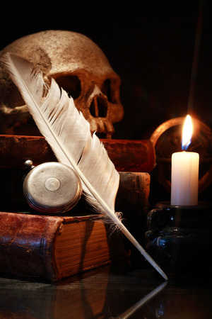 medieval medicine: Vintage still life with old books and quill near lighting candle Stock Photo