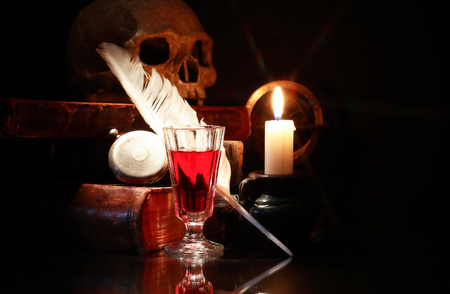 medieval medicine: Old books and quill near wine and lighting candle Stock Photo