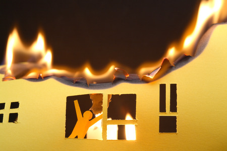burning house: Paper man in window of burning house on dark background