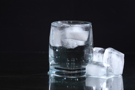 coolness: Glass of water with ice cubes on dark background