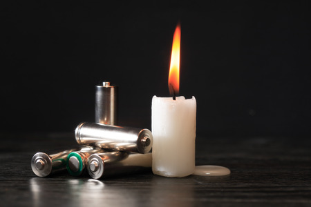 disconnection: Few batteries near lighting candle on dark background