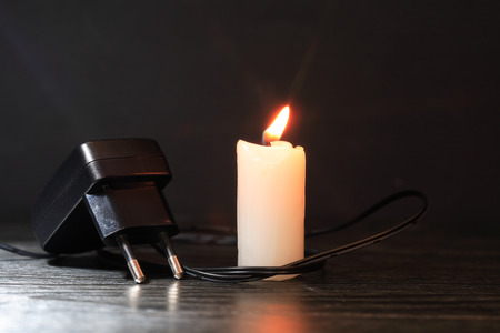 disconnection: Electric charger with cable near lighting candle on dark background