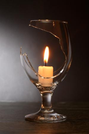 Lighting candle inside broken wineglass on dark background