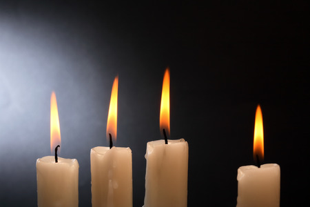 lighting background: Few lighting candles in a row on dark background Stock Photo