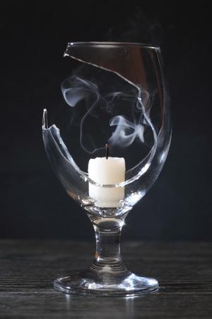 splinter: Extinguished candle with smoke inside broken wineglass on dark background Stock Photo