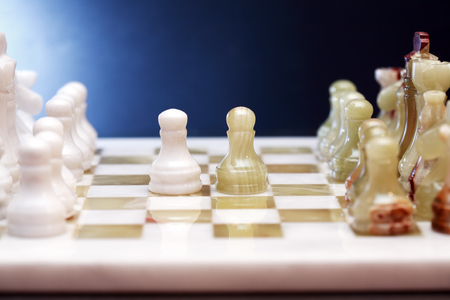 onyx: Chess pieces made from Onyx on board against blue background Stock Photo