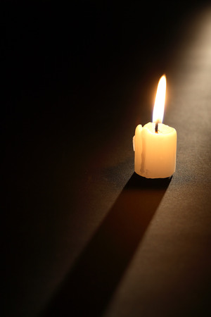 lighting background: One lighting candle with long shadow on dark background Stock Photo