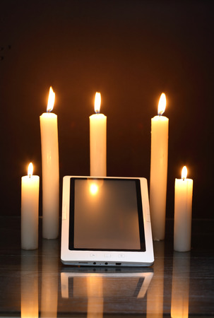 disconnection: Blackout concept. Lighting candles around tablet like a sanctuary