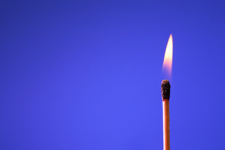 matchstick: Lighting matchstick on blue background with free space for text