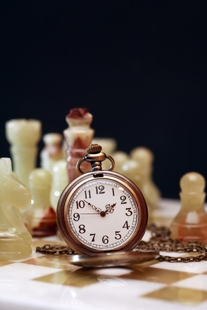 tablero de ajedrez: reloj de bolsillo de la vendimia en el tablero de ajedrez contra el fondo oscuro