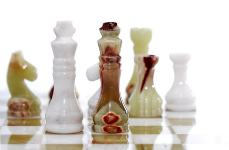 onyx: Chess pieces made from Onyx on board against white background Stock Photo