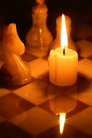 tablero de ajedrez: Set of chess pieces made from onyx against lighting candle on chessboard