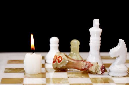 tablero de ajedrez: Concepto del triunfo. Iluminación de la vela en el tablero de ajedrez contra el fondo oscuro Foto de archivo