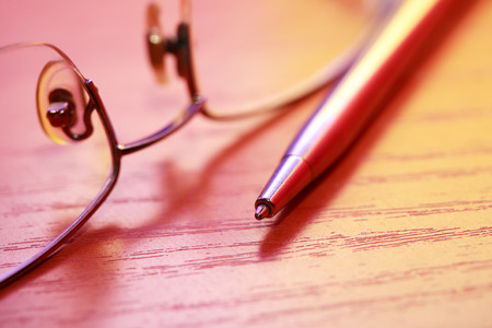 colorful still life: Colorful still life with pen near spectacles on wooden table Stock Photo