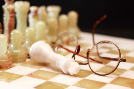 onyx: Set of chess pieces made from Onyx on board near spectacles against dark background
