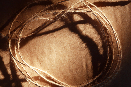 skein: Skein of twine on old brown paper with shadow