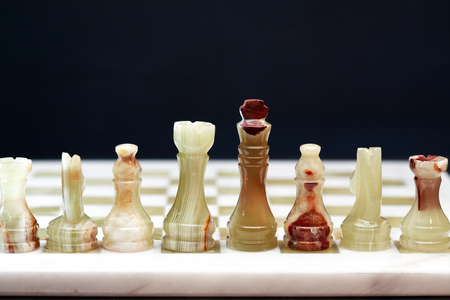 onyx: Set of chess pieces made from Onyx against dark background