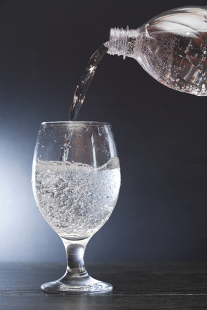 Mineral water flowing from bottle to glass on dark background