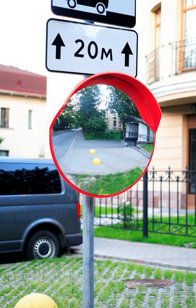 metal pole: Urban scene. Closeup of metal pole with road sign and big circle mirror