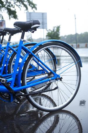 sotto la pioggia: Urban scene. Wet bicycles on parking under rain Archivio Fotografico