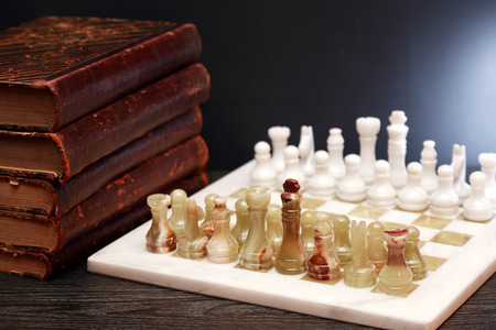 onyx: Set of chess pieces made from Onyx on board near books