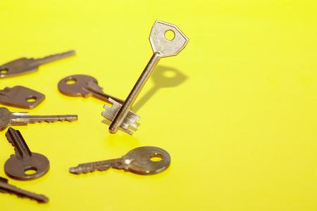 Individuality concept. One key standing near keys set lying on yellow background