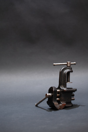 vice grip: Old metal vise on dark background with free space for text