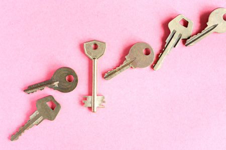 think safety: Abstract composition with door keys on pink paper background