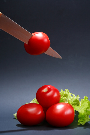 Cooking concept. Few freshness red tomatoes and knife on dark background Reklamní fotografie