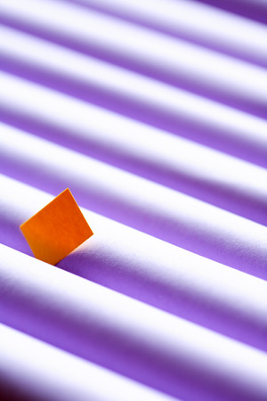 small paper: Individuality concept. One yellow small paper square between set of violet paper tubes