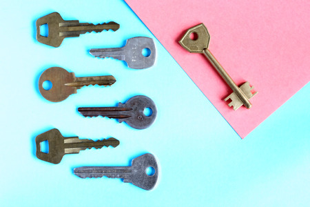 think safety: Abstract composition with door keys on blue paper background