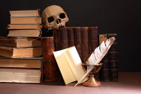 ビンテージのライブラリ。暗い背景上の行の古い本で人間の頭蓋骨