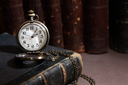 cover background time: Vintage library. Vintage pocket watch near books in a row on dark background