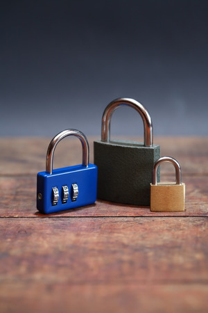 Three padlocks on wooden boaed against dark background