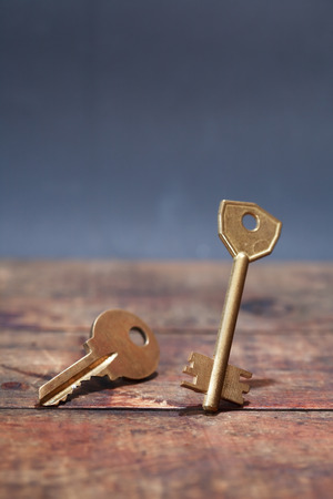 think safety: Door key standing on wooden board against dark background