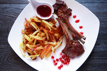 Plate with grilled lamb chops and fried potato on dark wooden table