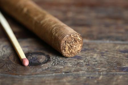 One Cuban cigar near matchstick on old wooden board